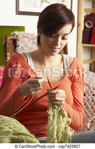 Young Woman Sitting In Chair Knitting - csp7423907
