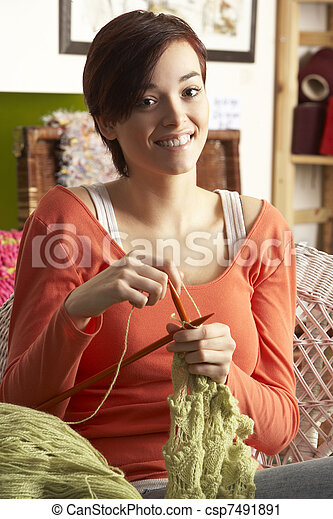 Young Woman Sitting In Chair Knitting - csp7491891