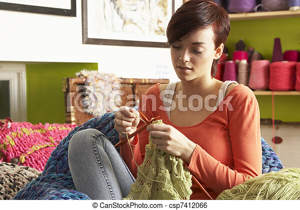 Young Woman Sitting In Chair Knitting - csp7412066