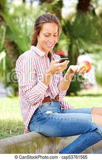 young woman sitting in park eating an apple and sending text message on mobile phone - csp53761565