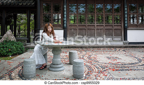 Young woman sitting on a chair in the garden Blossoms - csp9955029