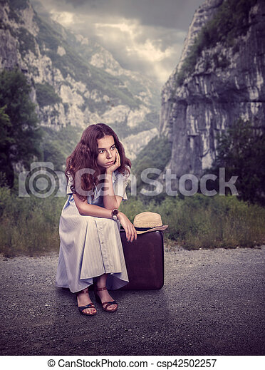 Young woman sitting on her suitcase. - csp42502257