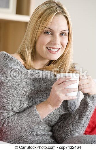 Young Woman Sitting On Sofa With Cup Of Coffee - csp7432464