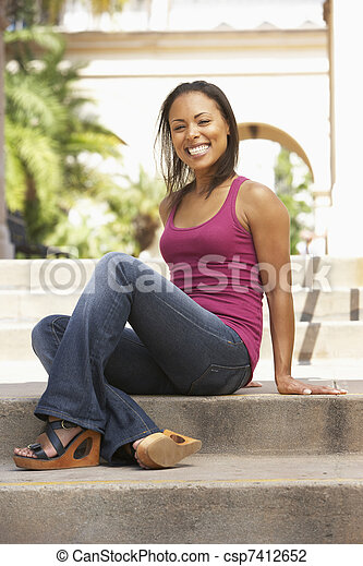 Young Woman Sitting On Steps Of Building - csp7412652