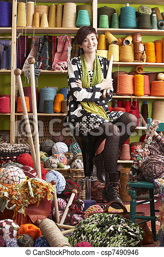 Young Woman Sitting On Stool Holding Knitting Needles In Front Of Yarn Display - csp7490946