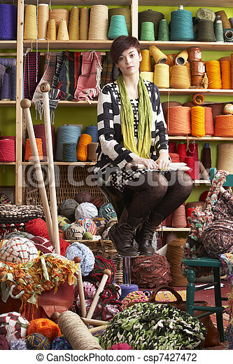 Young Woman Sitting On Stool Holding Knitting Needles In Front Of Yarn Display - csp7427472