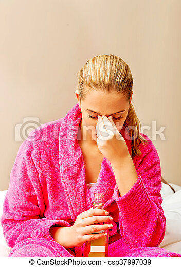 Young woman sitting on the bed crying and drinking whiskey - csp37997039
