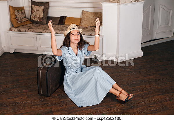Young woman sitting on the floor nearby suitcase. - csp42502180