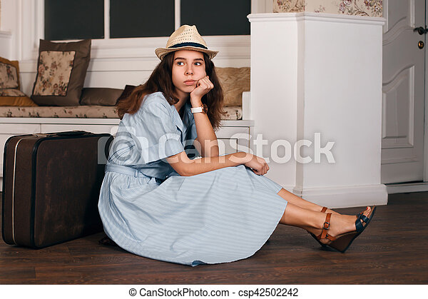 Young woman sitting on the floor nearby suitcase. - csp42502242