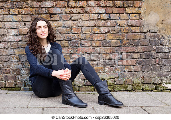 young woman sitting up against a brick wall - csp26385020