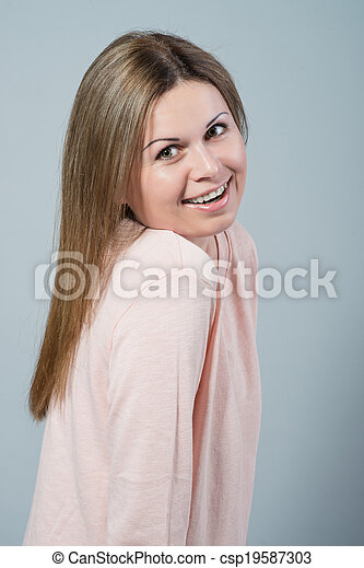 young woman smiling on grey background - csp19587303