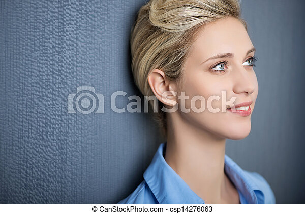 Young Woman Smiling While Looking Away Against Blue Wall - csp14276063