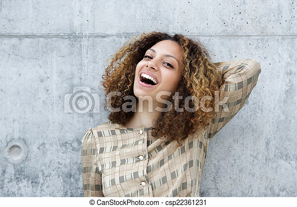 Young woman smiling with hand in hair - csp22361231