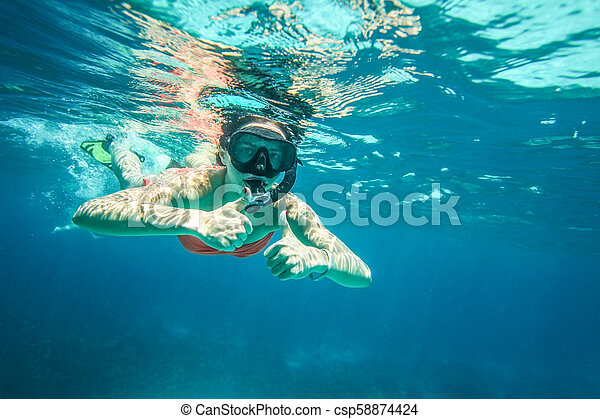 Young woman snorkel, holding two thumbs up, Similan Islands (Phang Nga), Thailand, one of the best snorkeling locations in Andaman sea. - csp58874424
