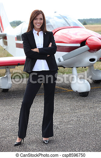 Young woman standing in front of an airplane - csp8596750
