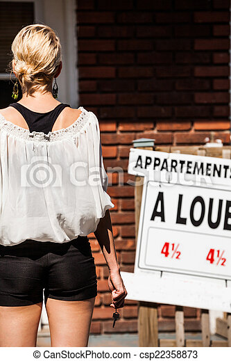 Young Woman standing in front of her new apartment - csp22358873