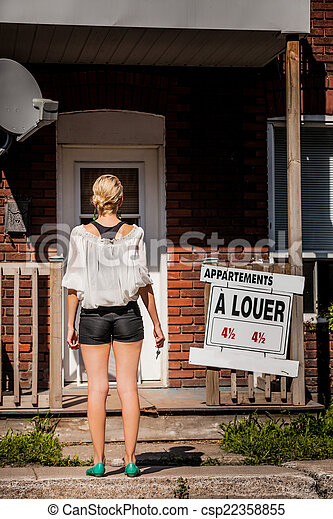 Young Woman standing in front of her new apartment - csp22358855