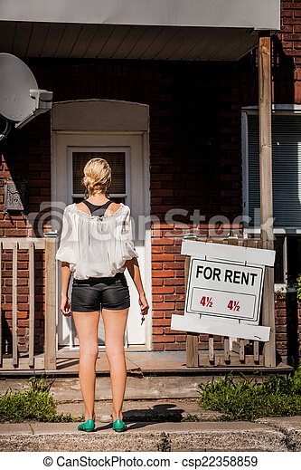 Young Woman standing in front of her new apartment - csp22358859