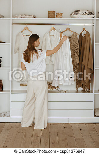 Young woman standing in front of her closet. - csp81376947