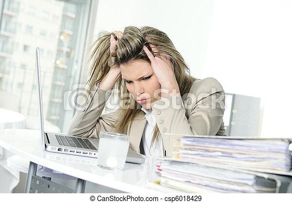 young woman stressed at work, taking an aspirin cahet - csp6018429