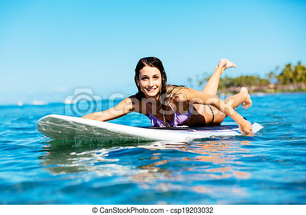 Young Woman Surfing In Hawaii Paddling Out To The Lineup