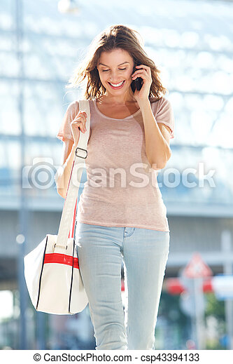 young woman talking on the phone and walking in the city - csp43394133