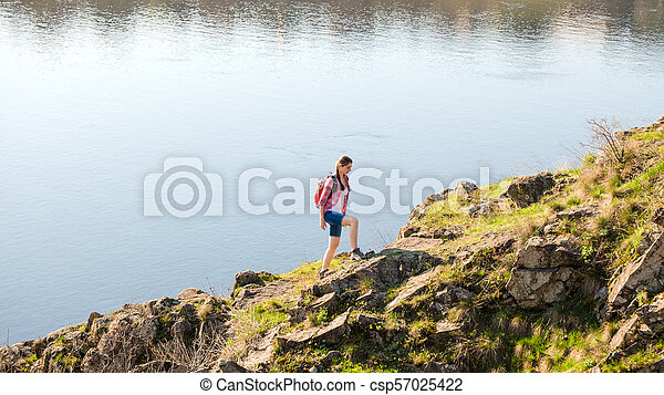 Young Woman Traveler with Backpack Climbing on Beautiful Rock at Warm Sunny Evening. Travel and Adventure Concept. - csp57025422