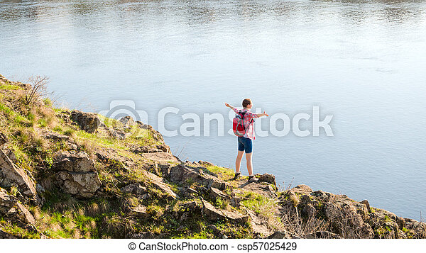 Young Woman Traveler with Backpack Enjoing Landscape on Beautiful Rock at Sunny Evening. Travel and Adventure Concept. - csp57025429