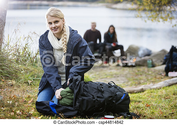 Young Woman Unpacking Backpack At Campsite - csp44814842