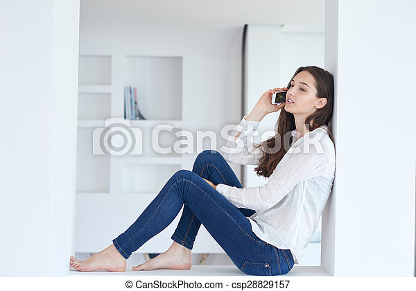 young woman using cellphone at home - csp28829157