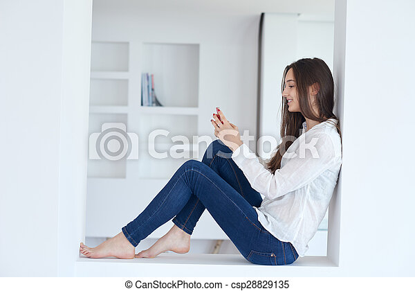 young woman using cellphone at home - csp28829135