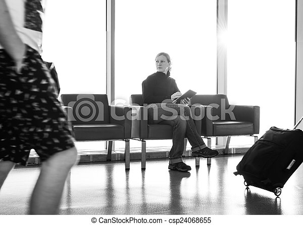 Young woman using her digital tablet pc at an airport lounge, with backlight. - csp24068655