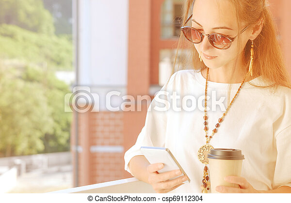 Young woman using mobile phone while drinking coffee on balcony. - csp69112304