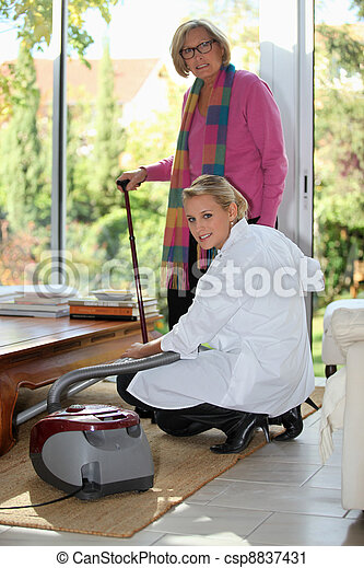 Young woman vacuuming for an elderly lady - csp8837431