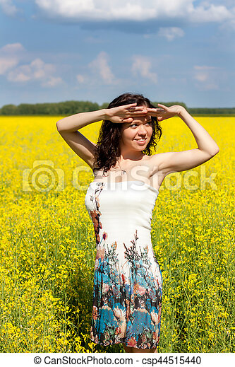Young woman walking on a field of yellow flowers - csp44515440