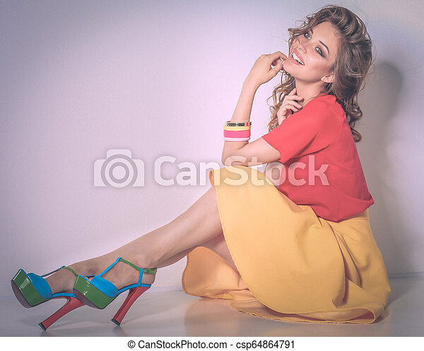 Young woman wearing a pink dress standing - csp64864791