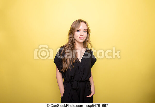Young woman wearing black dress on yellow background - csp54761667