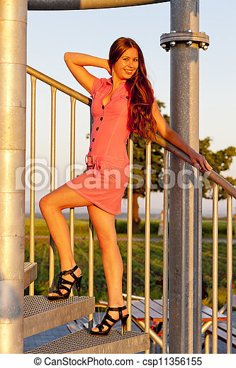 young woman wearing pink dress standing on stairs - csp11356155