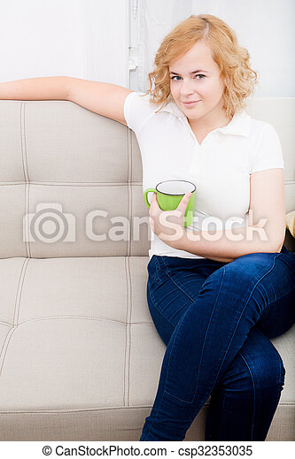 Young woman with a cup of coffee on the sofa - csp32353035