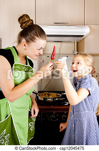 young woman with a daughter in the kitchen preparing - csp12045475