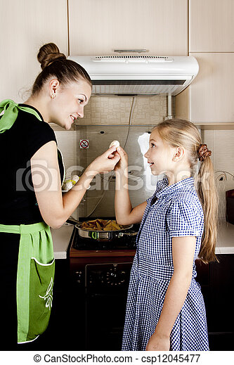 young woman with a daughter in the kitchen preparing - csp12045477