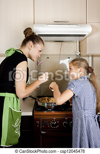 young woman with a daughter in the kitchen preparing - csp12045478