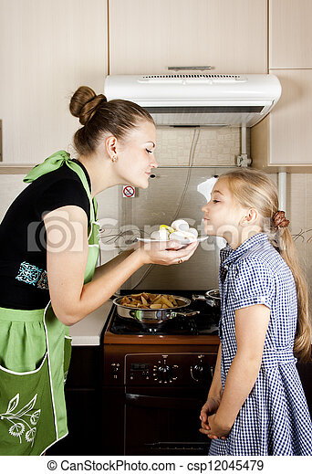 young woman with a daughter in the kitchen preparing - csp12045479
