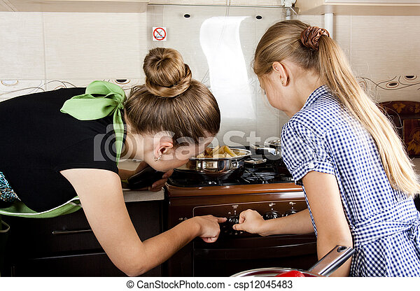 young woman with a daughter in the kitchen preparing - csp12045483