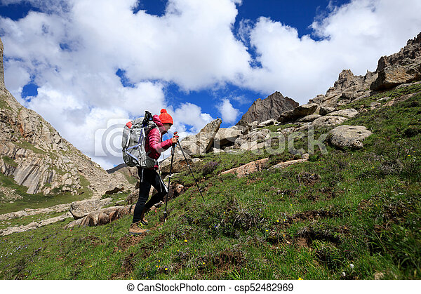 young woman with backpack hiking in mountains - csp52482969