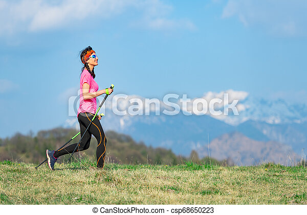 Young woman with braids in her hair during a sport walk in the mountains - csp68650223