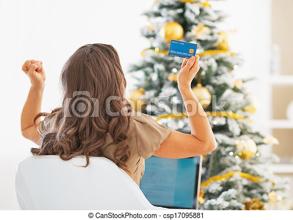 Young woman with credit card and laptop rejoicing success near christmas tree - csp17095881