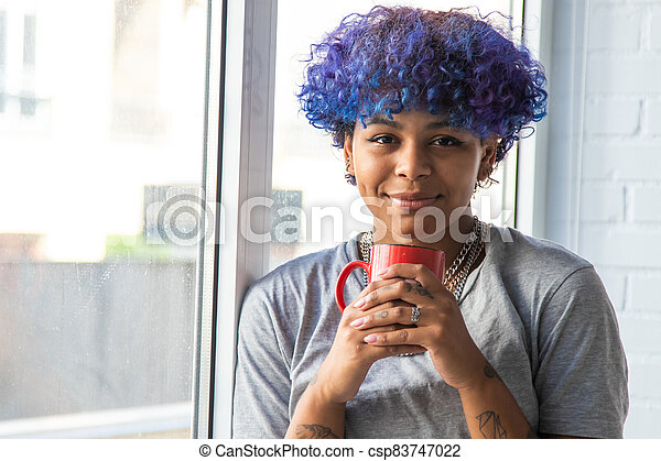 young woman with cup of coffee at the window - csp83747022