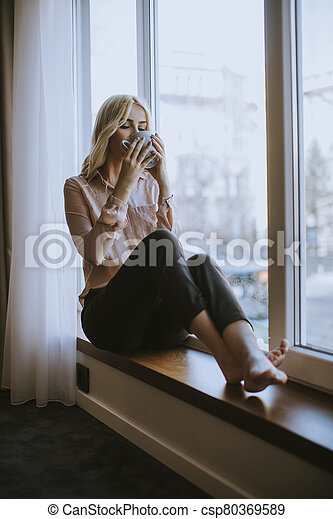 Young woman with cup of tea or coffee sitting and drinking on the window sill at home - csp80369589