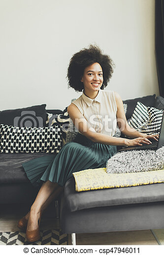 Young woman with curly hair, uses laptop and sitting on the sofa at home - csp47946011